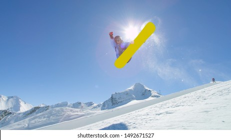 Young pro snowboarder riding the half pipe in big mountain snow park, performing spraying trick on halfpipe wall lip in sunny winter