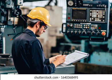 young profession technician engineer operate heavy machine to automated CNC in factory, worker with check list.