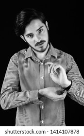 Young professional adult doing cuff button up on check business shirt. Concept, dressing for job interview. Monotone, black and white for dramatic effect dark and moody series.