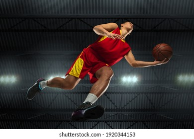 Young professional basketball player in action, motion isolated on black background, look from the bottom. Concept of sport, movement, energy and dynamic, healthy lifestyle. Training, practicing.