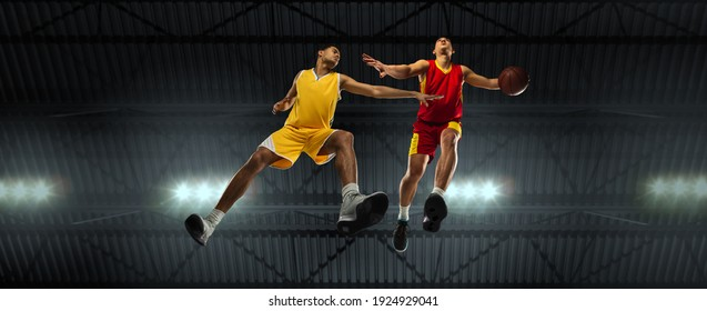 Young professional basketball players in competitive fight, motion in flight on black background, look from the bottom. Concept of sport, movement, energy and dynamic. Training, practicing. Flyer.