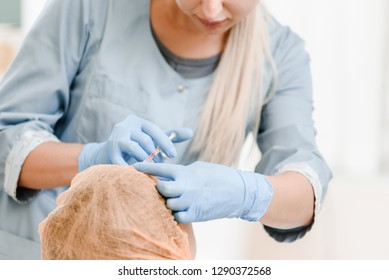 Young professional beautician doing injection for hair growth stimulation