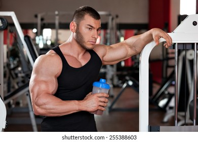 young professional bodybuilder in the gym, drinking a protein shake