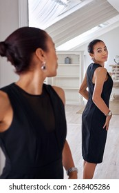young professional business woman checking elegant dress in mirror reflection at home bedroom