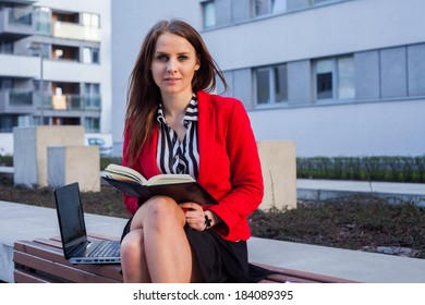 Young professional business woman sitting outdoor with computer laptop. In the background office block