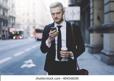 Young professional businessman using modern smartphone outdoors, successful lawyer wearing black suit and using his cellphone while going to the work and take taxi