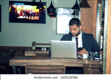 Young professional businessman wearing suit and using modern laptop, successful manager working in cafe during break and searching information in internet on his portable computer
