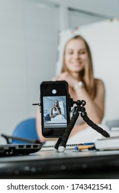 Young professional businesswoman vlogger coach talking to camera. Female blogger recording video. Filming live video blog or vlog, giving business class presentation, training teaching people online