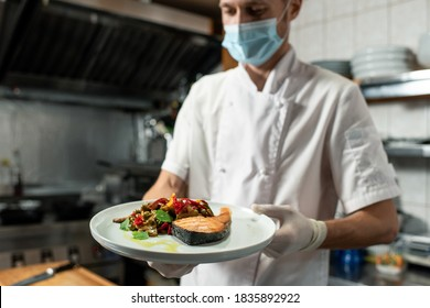 Young professional chef in white uniform and protective mask and gloves holding plate with fried salmon and vegetable garnish in the kitchen