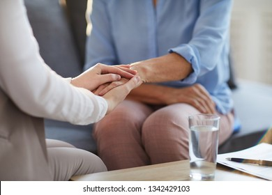 Young professional counselor holding hand of mature woman while giving her advice and supporting her