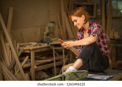 Young and professional craftswoman sitting on tabletop and holding phone in hands. Beautiful woman with ginger hair looking at phone and smiling. Joiner's shop interior.