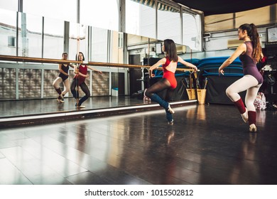 Young professional dancers training ballet in small studio with mirror.