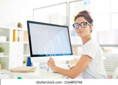 Young professional designer looking at you while sitting by desk in front of computer screen
