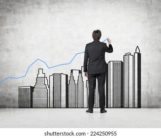 Young professional drawing a growing real estate chart. Concrete background.