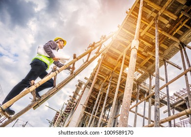 young professional engineer worker in protective helmet and blueprints paper on hand working on ladder at the house building construction site