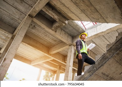 young professional engineer worker in protective helmet and blueprints paper on hand at the house building construction site