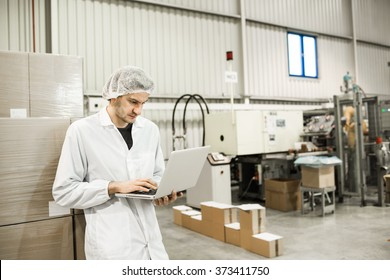 Young professional is leaning on the boxes in warehouse for food packaging. Manager is working on the computer in automated production line at modern factory. Color toned image.
