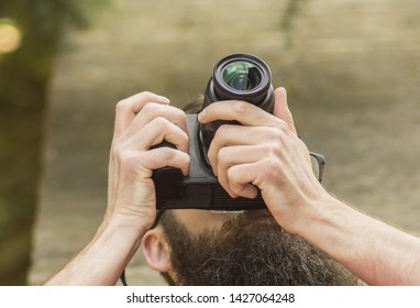 Young professional male photographer shooting outdoor on modern camera, empty area with copy space for your content, design or text message, flare light effect, man photographer taking photo outdoor