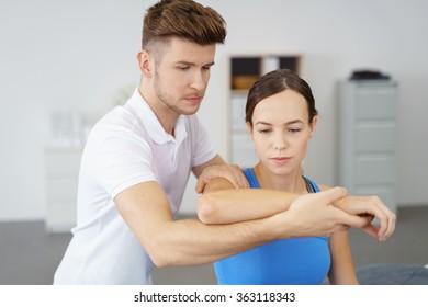 Young Professional Male Physical Therapist Examining the Arm of a Female Patient Inside the Clinic.