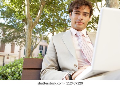 Young professional man using a laptop pc while sitting on a bench in a classic city square.
