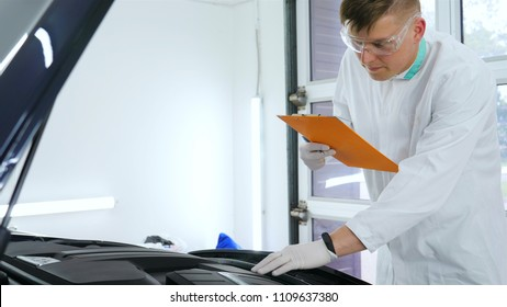 A young professional master will test the car engine, writes in a notebook, in a white coat, goggles, white rubber gloves, service machines.