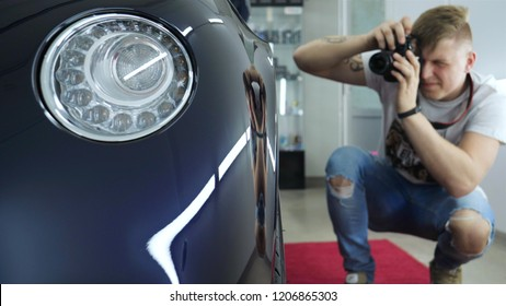 A young professional photographer (a guy, a man) takes pictures of a car in a car salon. Concept: lifestyle, new photo, car, photo camera, flash.