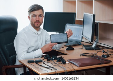 Young professional. Polygraph examiner works in the office with his lie detector's equipment.