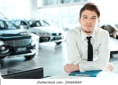 Young professional.  Portrait of handsome young sales man in formalwear posing with a note pad in car dealership