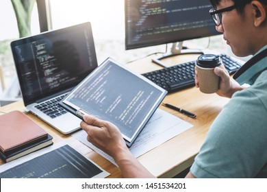 Young Professional programmer working at developing programming and website working in a software develop company office, writing codes and typing data code, Programming with HTML, PHP and javascript.