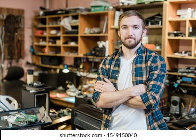 Joven reparador profesional de artilugios rotos cruzando los brazos en el pecho mientras estaba parado frente a la cámara en su taller