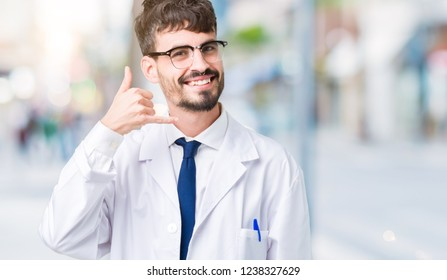 Young professional scientist man wearing white coat over isolated background smiling doing phone gesture with hand and fingers like talking on the telephone. Communicating concepts.