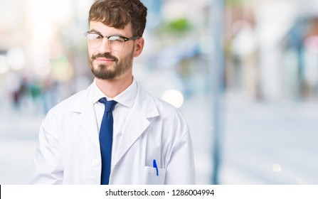 Young professional scientist man wearing white coat over isolated background winking looking at the camera with sexy expression, cheerful and happy face.