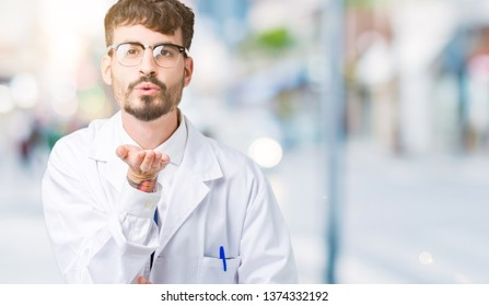 Young professional scientist man wearing white coat over isolated background looking at the camera blowing a kiss with hand on air being lovely and sexy. Love expression.
