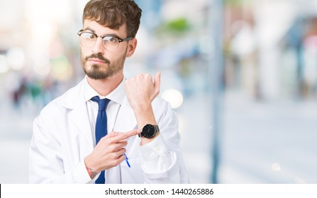 Young professional scientist man wearing white coat over isolated background In hurry pointing to watch time, impatience, upset and angry for deadline delay