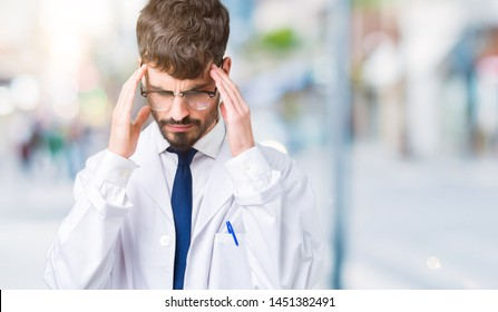 Young professional scientist man wearing white coat over isolated background with hand on head for pain in head because stress. Suffering migraine.