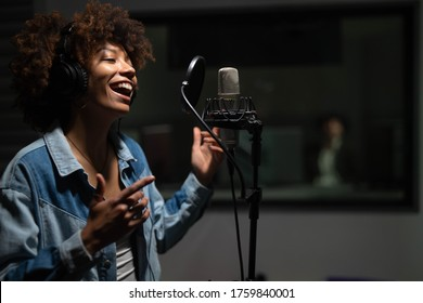 An young professional smiling energetic african female singer wearing headphones is performing a new song with a microphone while recording it in a music studio.