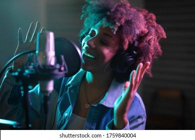 Eine junge professionelle Sängerin mit Kopfhörern, die energetisch lächelt, spielt ein neues Lied mit einem Mikrofon und nimmt es in einem Musikstudio mit bunten Lichtern auf einem Hintergrund auf.