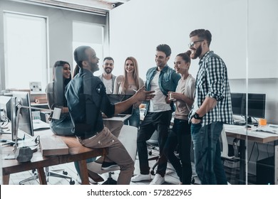 Young professional team.  Group of young modern people in smart casual wear having a brainstorm meeting while standing behind the glass wall in the creative office