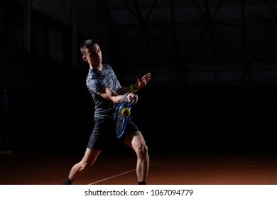 young professional tennis player with a blue racket hitting a forehand, black background