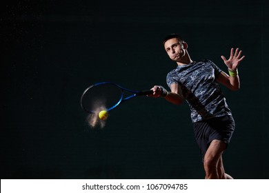 young professional tennis player with a blue racket hitting a forehand, black background, wet ball creating a splash