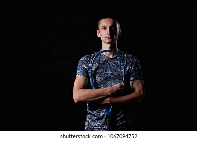 young professional tennis player holding a blue racket, on black background
