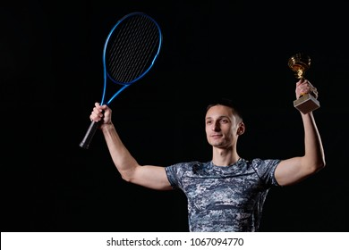 young professional tennis player holding a trophy, blue racket, black background