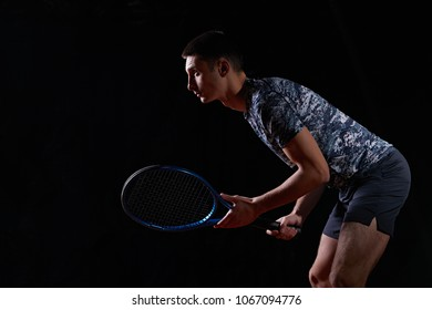 young professional tennis player holding a blue racket, on black background, waiting to return a serve