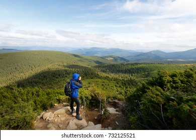 Young professional traveller man with dslr camera shooting outdoor fantastic mountain landscape. Hiker stands on a rock at the high summit and photographing