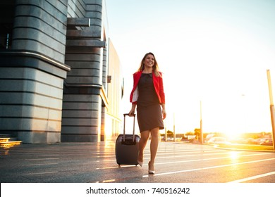 A young professional woman arriving at the airport and walking towards her car.