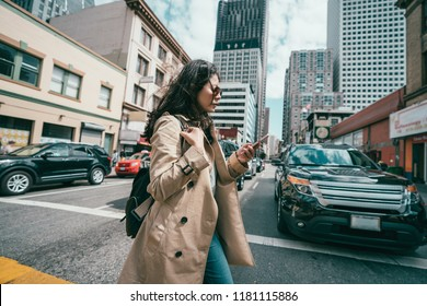 young professional woman crossing the road while using her mobile phone when cars waiting.