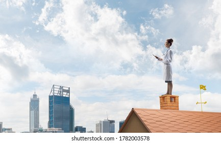 Young but professional woman doctor in medical suit standing at the edge of brick roof and looking away, with cloudy skyscape and city view on background. Medical industry concept