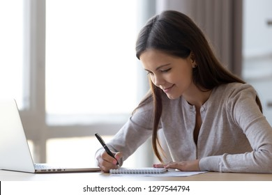 Young professional woman intern student noting in notebook studying at home office, teen girl writing essay or preparing for test exam with laptop, copywriter freelancer making list planning tasks