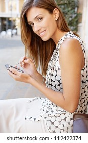 Young professional woman using a smart phone and electronic pen in a classic city, smiling.