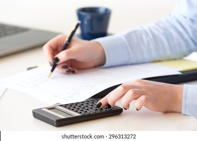 Young professional woman works on financial  reports of a company by using technological tools and equipments.She evaluates the performance and success of the management of divisions in a company.